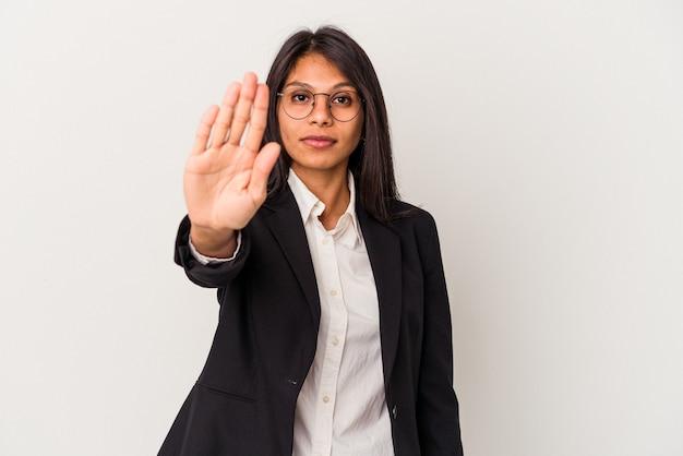 一時停止の標識を示す伸ばした手で立っている白い背景で隔離の若いビジネスラテン女性は、あなたを防ぎます。