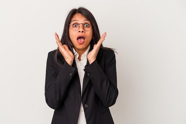 白い背景で隔離の若いビジネスラテン女性は驚いてショックを受けました。