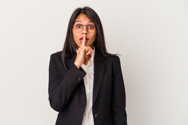 Young business latin woman isolated on white background keeping a secret or asking for silence.