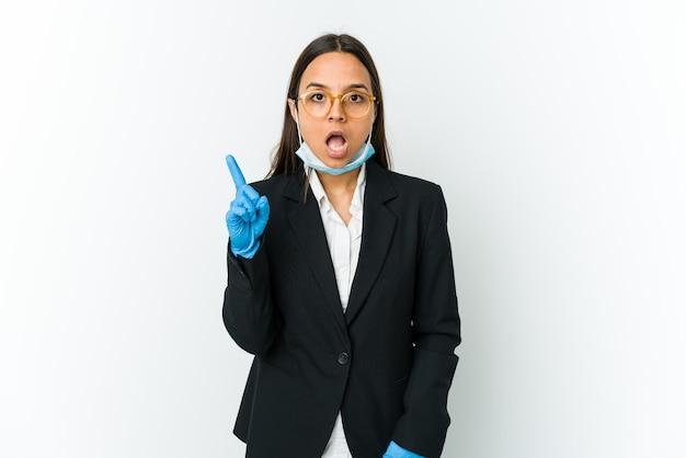 Молодой бизнес латинской женщины в маске для защиты от covid, изолированные на белом фоне, имея идею, концепцию вдохновения.