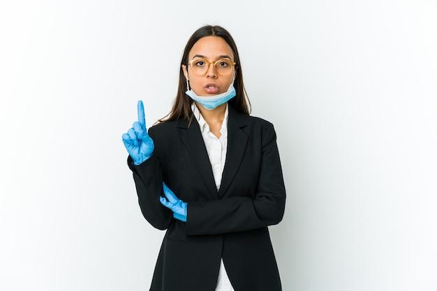 Молодой бизнес латинской женщины в маске для защиты от covid, изолированные на белом фоне, имея отличную идею, концепцию творчества.