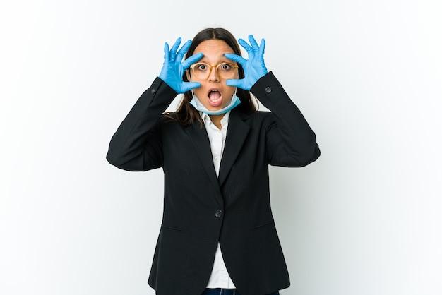 Молодая деловая латинская женщина в маске для защиты от covid изолирована на белом, держа глаза открытыми, чтобы найти возможность успеха.