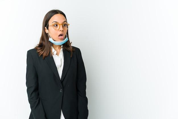 彼女が見た何かのためにショックを受けている白い壁に隔離されたcovidから保護するためにマスクを身に着けている若いビジネスラテン女性。