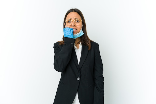 指の爪を噛む白い壁に隔離されたcovidから保護するためにマスクを身に着けている若いビジネスラテン女性、神経質で非常に不安