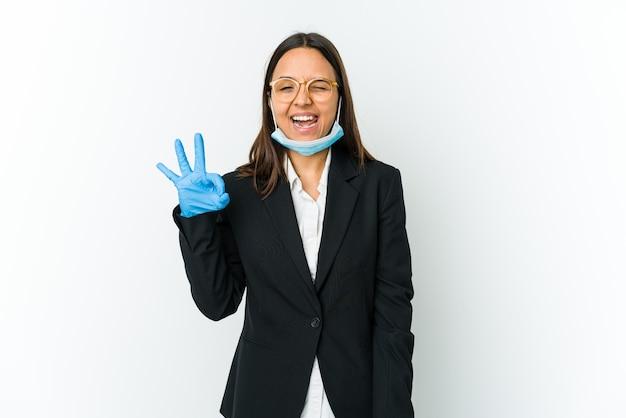 Молодая деловая латинская женщина в маске для защиты от covid, изолированной на белой стене, подмигивает и держит рукой жест.