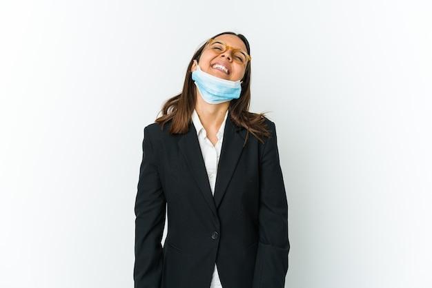 Молодая деловая латинская женщина в маске для защиты от covid на белом расслабленно и счастливо смеется, вытянув шею, показывая зубы.