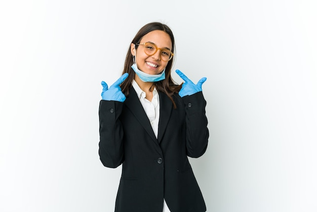Young business latin woman wearing a mask to protect from covid isolated on white,  smiles, pointing fingers at mouth.