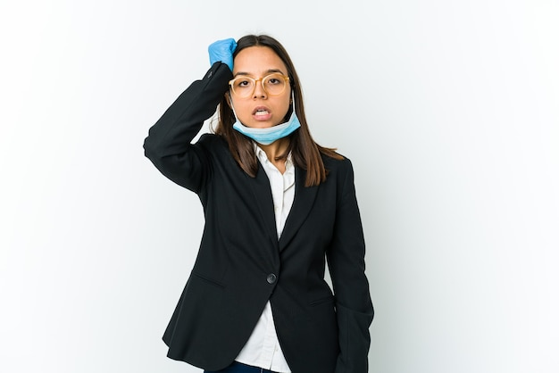 Young business latin woman wearing a mask to protect from covid isolated on white wall tired and very sleepy keeping hand on head.
