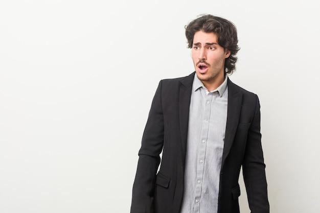 ショックを受けている白い壁に対して若いビジネスマン