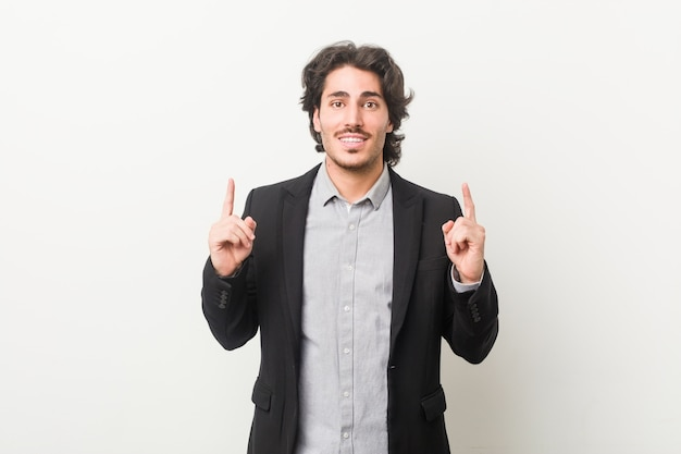 Young business man against a white wall indicates with both fore fingers up showing a blank space.