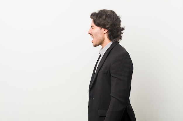 Young business man against a white wall shouting towards a copy space
