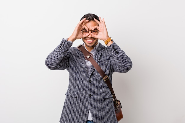 Young business man against a white wall showing okay sign over eyes