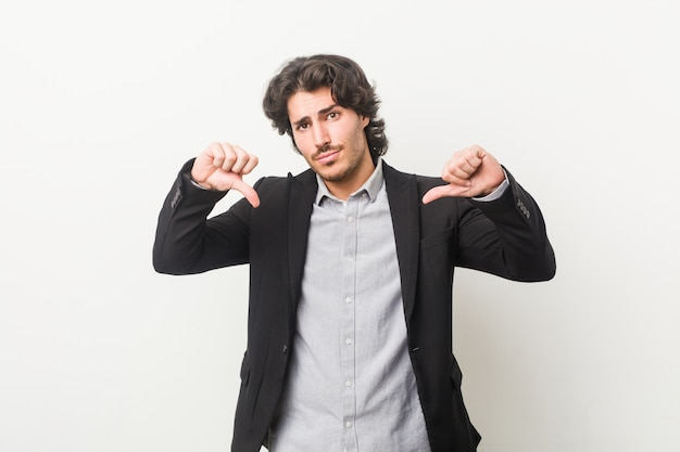 Young business man against a white wall showing thumb down and expressing dislike.