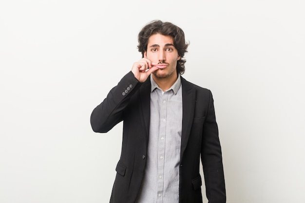 Young business man against a white wall with fingers on lips keeping a secret.