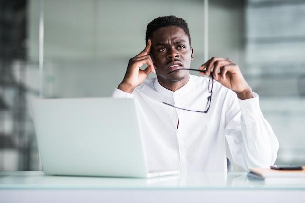 彼の職場で若いビジネスマンは、手で頭の痛みに触れる頭を感じます。ストレスワーク