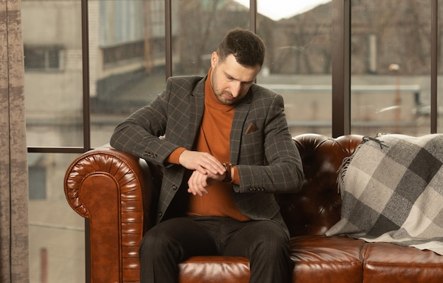 Young business man checking time on his watch and sitting on sofa