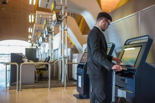 Young business man doing self check in a machine at the airport
