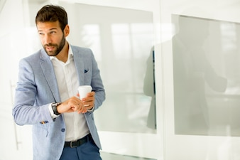 Young business man drinking coffee on break