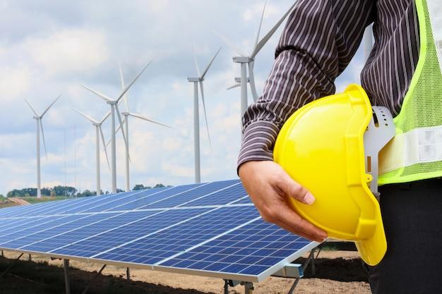 젊은 비즈니스 남자 엔지니어는 태양 전지 패널과 풍력 발전기 발전소 건설 현장 배경에서 노란색 헬멧을 개최