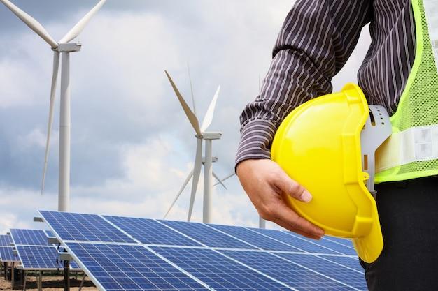 Молодой бизнесмен-инженер держит желтый шлем у солнечных панелей и ветряных генераторов