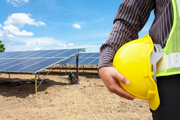 Молодой деловой человек инженер держит желтый шлем на фоне строительной площадки электростанции солнечных батарей