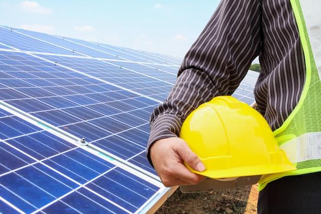 젊은 비즈니스 남자 엔지니어는 태양 전지 패널 발전소 건설 현장에서 노란색 헬멧을 개최