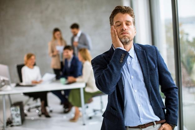 疲れ果ててオフィスの彼の職場に立つ若いビジネスマン