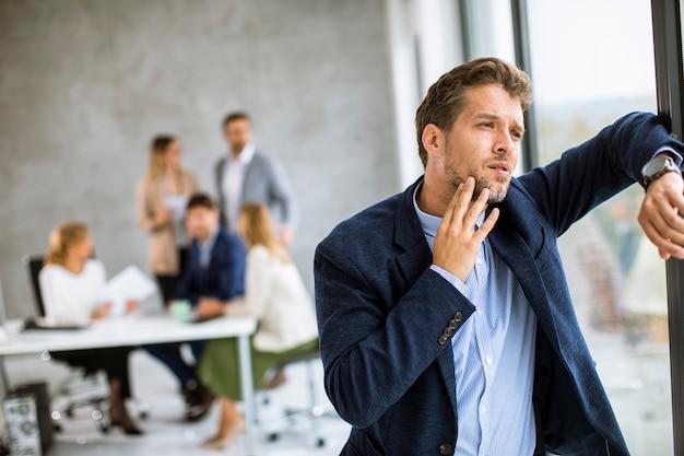 지친 느낌과 사무실에서 자신의 작업 장소에 서있는 젊은 비즈니스 사람