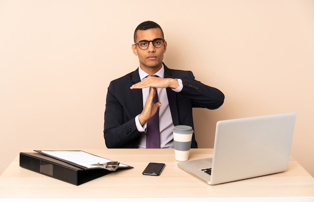 Young business man in his office with a laptop and other documents making time out gesture