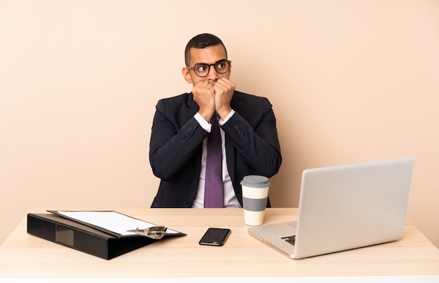 Young business man in his office with a laptop and other documents nervous and scared putting hands to mouth