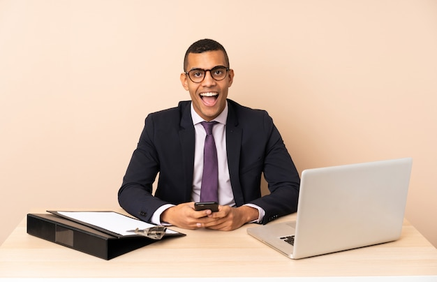 Young business man in his office with a laptop and other documents surprised and sending a message