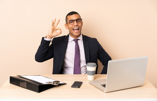 Young business man in his office with a laptop and other documents surprised and showing ok sign