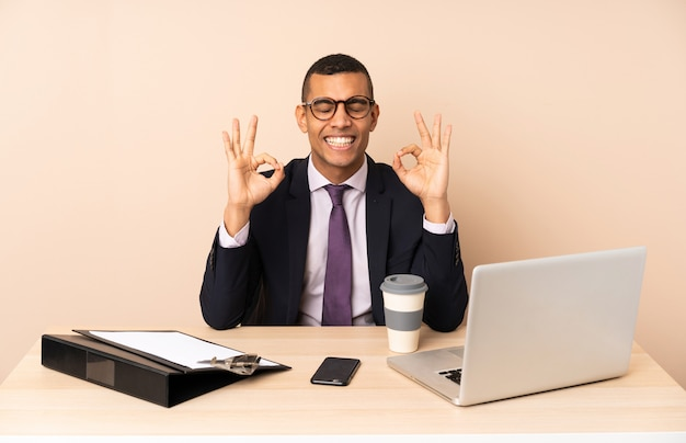 Young business man in his office with a laptop and other documents in zen pose