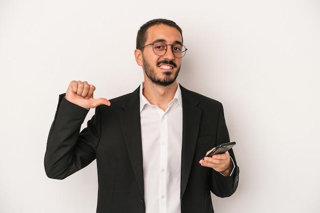 白い背景で隔離の携帯電話を持っている若いビジネスマンは、誇りと自信を持って、従うべき例を感じます。