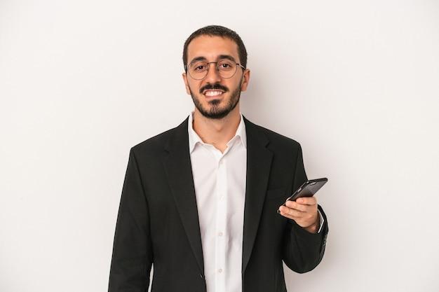幸せ、笑顔、陽気な白い背景で隔離の携帯電話を保持している若いビジネスマン。