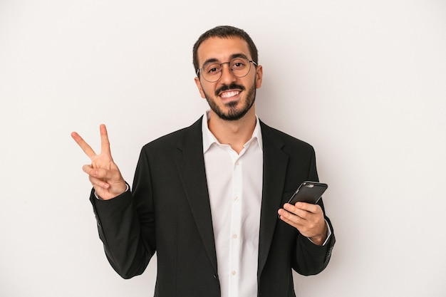 白い背景で隔離の携帯電話を持っている若いビジネスマンは、指で平和のシンボルを示して楽しくてのんき。