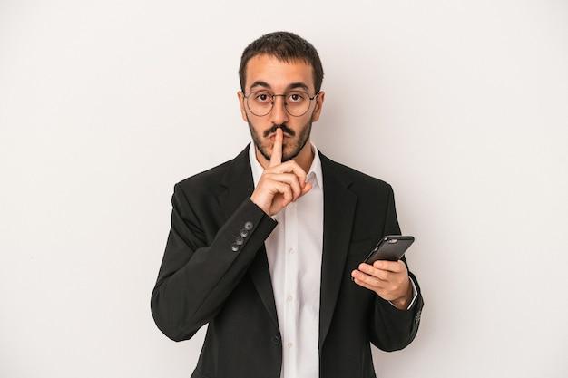 秘密を保持するか、沈黙を求めて白い背景で隔離の携帯電話を保持している若いビジネスマン。