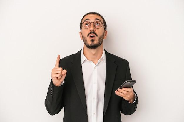 口を開けて逆さまを指している白い背景で隔離の携帯電話を保持している若いビジネスマン。