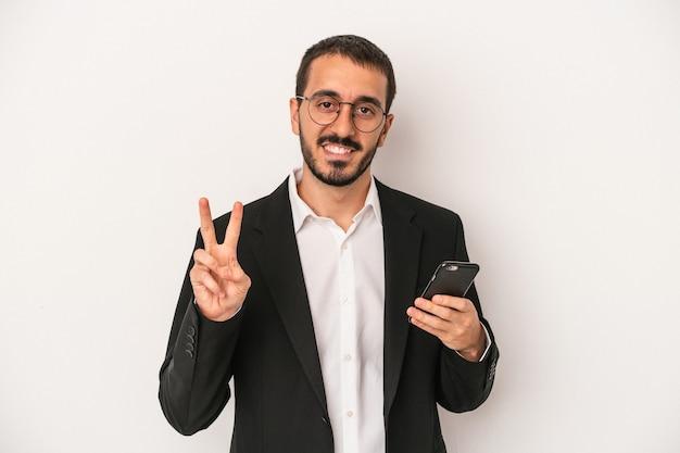指で2番目を示す白い背景で隔離の携帯電話を保持している若いビジネスマン。