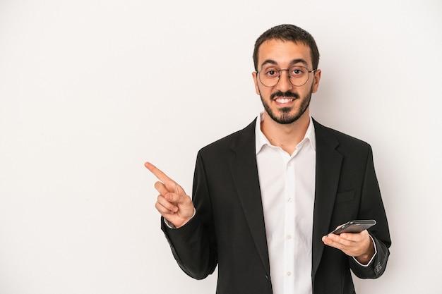 白い背景で隔離の携帯電話を持っている若いビジネスマンは、笑顔で脇を指して、空白のスペースで何かを示しています。