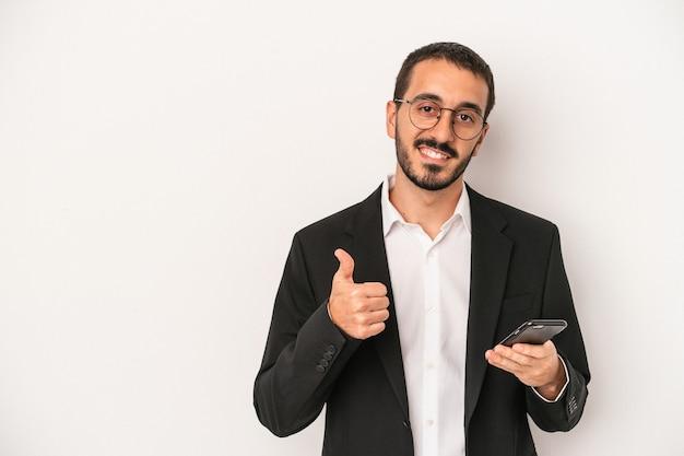 笑顔と親指を上げて白い背景で隔離の携帯電話を保持している若いビジネスマン