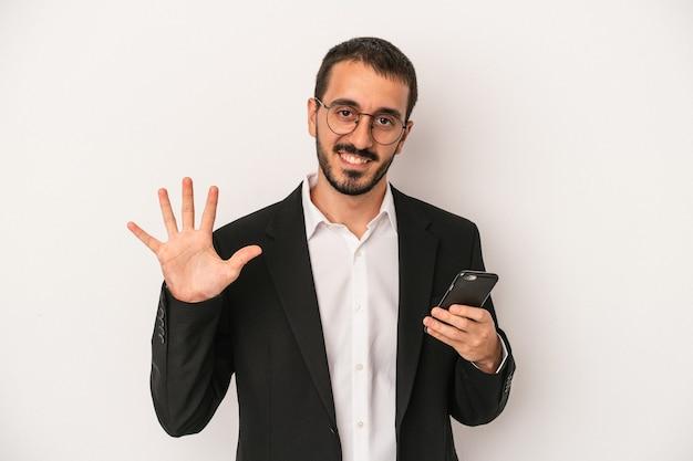 白い背景で隔離の携帯電話を持っている若いビジネスマンは、指で5番を示して陽気に笑っています。
