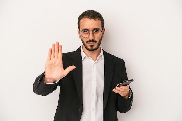 一時停止の標識を示す伸ばした手で立っている白い背景で隔離の携帯電話を保持している若いビジネスマンは、あなたを防ぎます。