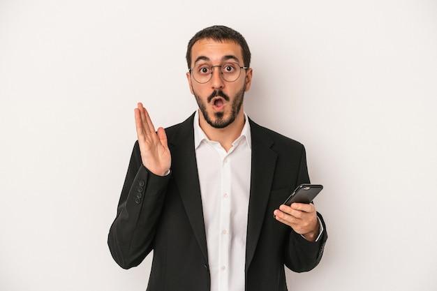 白い背景で隔離の携帯電話を保持している若いビジネスマンは驚いてショックを受けました。