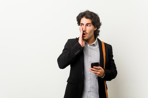 電話を持っている若いビジネスマンは秘密の急ブレーキのニュースを言っているとよそ見