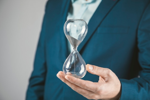 Young business man holding hourglass on grey