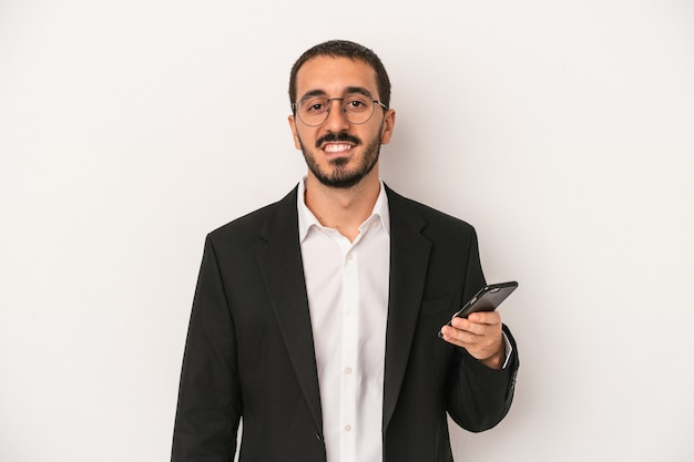 Young business man holding a mobile phone isolated on white background happy, smiling and cheerful.