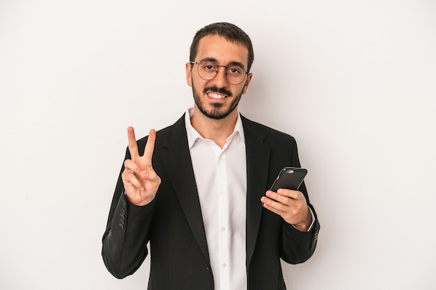 Young business man holding a mobile phone isolated on white background showing number two with fingers.