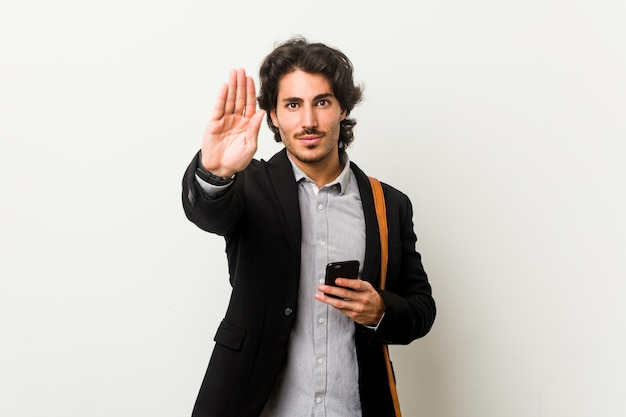 Young business man holding a phone standing with outstretched hand showing stop sign, preventing you