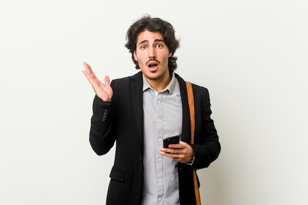 Young business man holding a phone surprised and shocked.